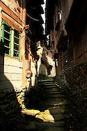 Small stone lane in a village of Ping'an lined with traditional wooden houses, Guangxi, China, Asia