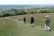 A group of walking friends on a public footpath, descend in single-file, the contours of the escarpment that overlooks the Kent village of Kemsing, on 13th June 2021, in Kemsing, Kent, England.