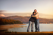 A couple embrace while standing in front of a beautiful lake.