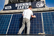 A man cleans solar panels on Nelsons column plinth in Trafalgar Square, on 8th October, 2019 in London, Untited Kingdom. Extinction Rebellion plan to occupy 12 sites situated around key Government locations around Westminster for two weeks to protest against climate change.
