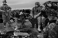 After a long mission of disposing improvised explosive devices, soldiers hang around a camp fire in Baghdad, Iraq, on Jan. 21, 2008.