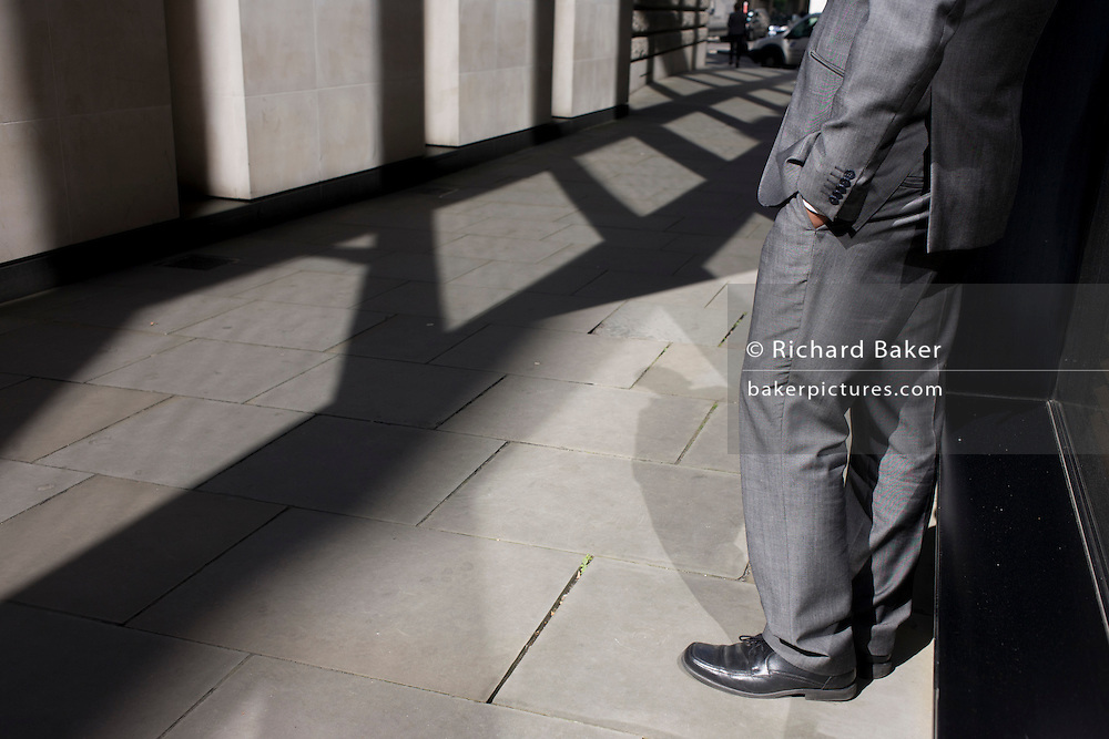 Anonymous man wearing shiny grey suit stands in narrow sunlit lane in the City of London.