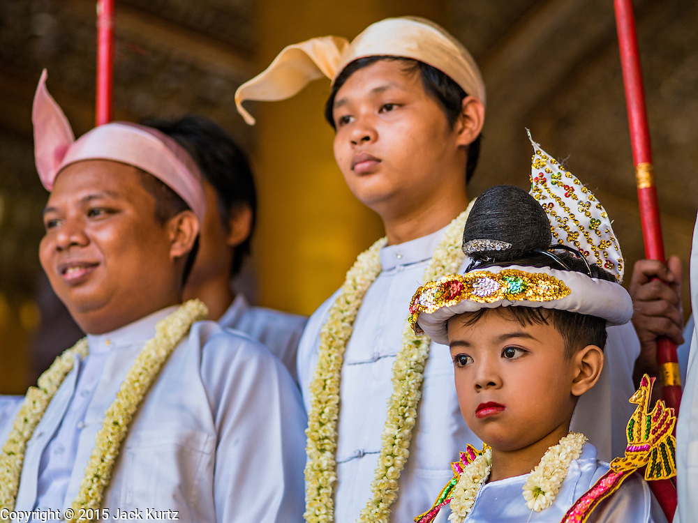 31 OCTOBER 2015 - YANGON, MYANMAR: A boy being ordained as a Buddhist novice (young monk) with some of his family at Shwedagon Pagoda. Shwedagon Pagoda is officially known as Shwedagon Zedi Daw and is also called the Great Dagon Pagoda or the Golden Pagoda. It is a 99 metres (325ft) tall pagoda and stupa located in Yangon, Burma. The pagoda lies to the west of on Singuttara Hill, and dominates the skyline of the city. It is the most sacred Buddhist pagoda in Myanmar and contains relics of four past Buddhas: the staff of Kakusandha, the water filter of Koṇāgamana, a piece of the robe of Kassapa and eight strands of hair from Gautama, the historical Buddha. The pagoda was built between the 6th and 10th centuries by the Mon people, who used to dominate the area around what is now Yangon (Rangoon). The pagoda has been renovated numerous times through the centuries. Millions of Burmese and tens of thousands of tourists visit the pagoda every year, which is the most visited site in Yangon.      PHOTO BY JACK KURTZ
