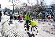 In Utrecht rijdt een man met een groene jas op een fiets met een groen fietskrat door de binnenstad.<br /> <br /> In Utrecht a man with a green jacket rides on a bike with a green basket in the city center.