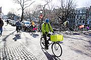 In Utrecht rijdt een man met een groene jas op een fiets met een groen fietskrat door de binnenstad.<br /> <br /> In Utrecht a man with a green jacket rides on a bike with a green basket in the city center.