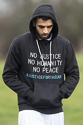 """© Licensed to London News Pictures. 06/01/2017. Huddersfield, UK. A man wearing a hoodie with """" No justice no humanity no peace #justiceforyassar"""" at the funeral of Yassar Yaqub at Hey Lane Cemmetary in Huddersfield, West Yorkshire. Yaqub, 28, from Huddersfield, was shot dead in a car stopped near junction 24 of the M62 as part of a planned police operation. Photo credit: Joel Goodman/LNP"""
