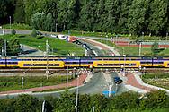 Nederland, Halfweg, 29 aug 2013<br /> Uitzicht vanaf de voormalige suikersilo's bij Halfweg op het spoor van de lijn Amsterdam, Haarlem.  Een trein rijd voorbij de spoorwegovergang.<br /> Foto(c): Michiel Wijnbergh