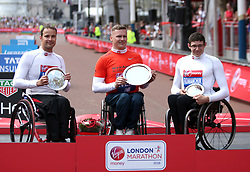 Great Britain's David Weir (centre) poses with the trophy after winning the Men's Elite alongside second placed Switzerland's Marcel Hug (left) and third placed USA's Daniel Romanchuk during the 2018 Virgin Money London Marathon.