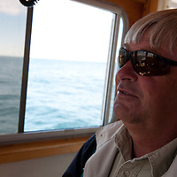 Captain Peter Wilcox, owner of Sea Watch Tours, on a birdwatching trip to Machias Seal Island. Captain Wilcox has had a role in tourism on Grand Manan Island for 40 years, seeing the ocean as a lobster fisherman and as a tour operator. In the Bay of Fundy, New Brunswick, Canada. Photo by William Drumm.