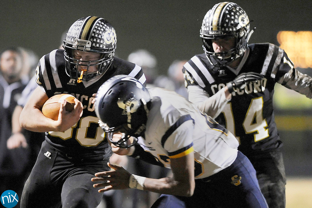 Spiders tight end Isaac Staton (80, left) is hit by a Vikings corner back Keaudre Morrison (23, right) after catching a pass during the South Iredell Vikings at Concord Spiders 3A high school football playoff game on Nov. 27.