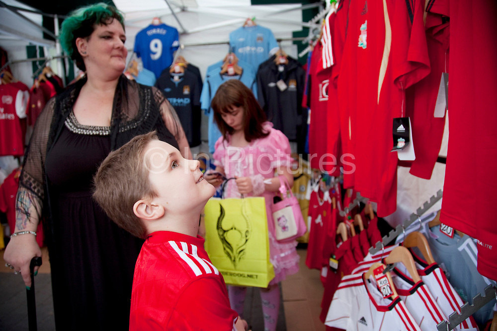 LONDON, ENGLAND, UK, JUNE 11TH 2011. Mother Louise Irwin-Ryan with her daughter Georgia (11, wearing a pink Lolita dress) and son Kiefer (8, wearing a red Liverpool Football Club kit) spending a day out together in Camden Town, North London. Kiefer wants to look at the football strips and asks if his mum can buy him the 2011 shorts. His mother explains that the 2009 shorts will have to do because they just can't afford it. Louise is on various benefits to help support her family income, and housing, although recent government changed to benefits may affect her family drastically, possibly meaning they may have to move out of London. Louise Ryan was born on the Wirral peninsula in 1970.  She moved to London with her family in 1980.  Having lived in both Manchester and Ireland, she now lives permanently in North London with her husband and two children. Through the years Louise has battled to recover from a serious motorcycle accident in 1992 and has recently been diagnosed with Bipolar Affective Disorder. (Photo by Mike Kemp/For The Washington Post)