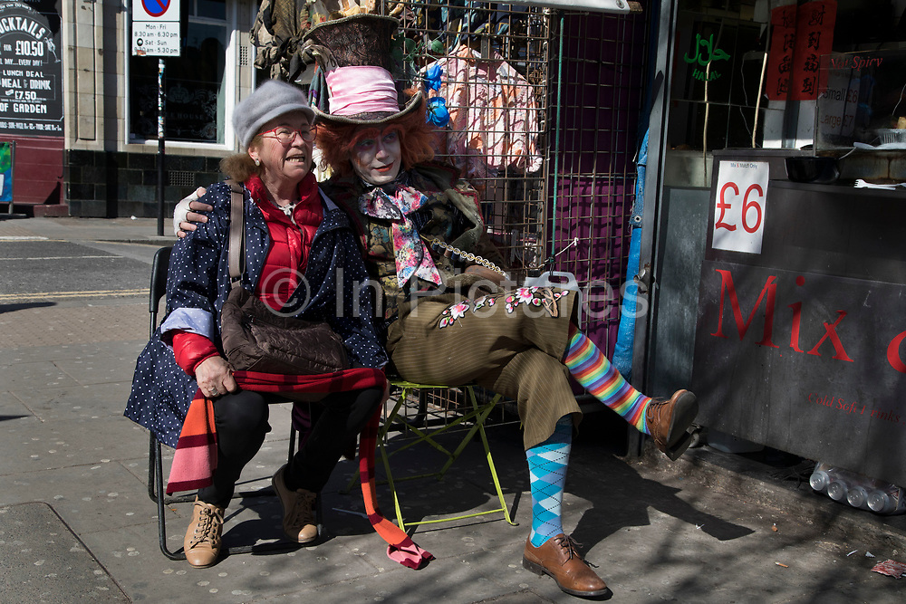 Street performer dressed up as the Mad Hatter, from the Alice in Wonderland story sits with a tourist in Camden Town, London, England, United Kingdom. Camden Town is famed for its market, warren of fashion and shops near Regent's Canal, and is a haven of alternative counter culture.