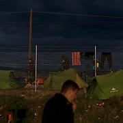 Migrants pass by tents set up near the border between Greece and Macedonia in Idomeni, Greece. Around 13,000 migrants and refugees, mostly from the Middle East and African nations, are believe to be stranded here awaiting a chance to proceed their journey towards Germany and other northern European countries.