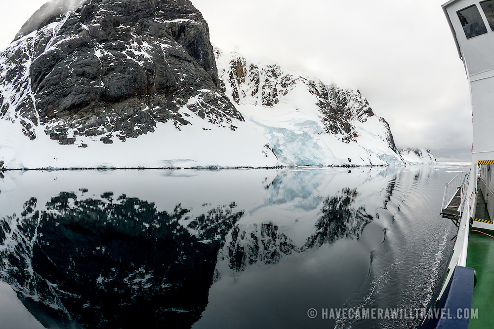"""An Antarctic cruise ship passes through glassy waters of the Lemaire Channel, as the mountains along the shore are reflected on the water. The Lemaire Channel is sometimes referred to as """"Kodak Gap"""" in a nod to its famously scenic views. At right can be seen part of a cruise ship."""
