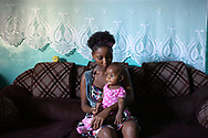 """CLIENT: POPULATION ACTION INTERNATIONAL<br /> <br /> Sylvian Musau, 21, and her daughter Chelsea Danela, 9 months, in the living room of their apartment in Mombasa, Kenya. On the eve of her 20th birthday, Sylvian became pregnant with Chelsea. Having no one to turn to during the pregnancy led her to become an outspoken safe sex advocate. She is part of a young mothers club, works with a project that addresses early and unsafe sex and has been named """"Miss Youth to Youth"""", speaking to youth groups about family planning options."""