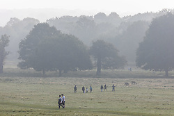 Licensed to London News Pictures. 09/10/2021. London, UK. Walkers enjoy the misty morning in Richmond Park south-west London as the Met Office issue yellow weather warnings for fog patches in London and the South East, leading to difficult driving conditions and disruption to travel. Photo credit: Alex Lentati/LNP