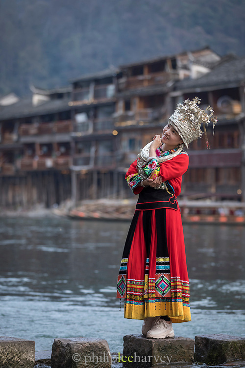 Full length shot of a teenage girl in traditional Miao clothing posing on stepping stones in a river, Fenghuang, Hunan Province, China