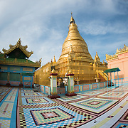 An ornately decorated courtyard in front of a gold stupa at Soon Oo Pon Nya Shin Pagoda. Sitting on top of Nga-pha Hill, Soon Oo Pon Nya Shin Pagoda is one of multiple pagodas and temples in the religious district of Sagaing, near Mandalay. The original pagoda dates to 674.