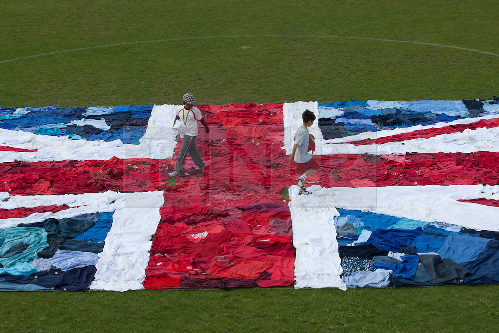 © licensed to London News Pictures. London, UK 09/08/2012. Children running on the world's largest Union Jack flag clothes mosaic in West Ham Park, East London. Using 2,100 unwanted items of clothing donated to the Shwopping initiative, M&S, local volunteers and Oxfam made the world's largest Union Jack flag clothes mosaic. The campaign aims to put an end to the one billion items currently ending up in landfill every year. Photo credit: Tolga Akmen/LNP