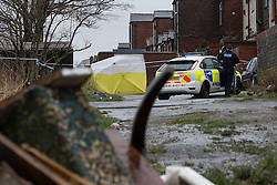 © Licensed to London News Pictures . 15/02/2014 . Oldham , UK . Police and crime scene investigators close off an alleyway behind terraces parallel to Ripponden Road this morning (15th February 2014) where it is reported the body of a fifteen year old boy - named locally as Leon Cudworth - was discovered in the early hours . Photo credit : Joel Goodman/LNP