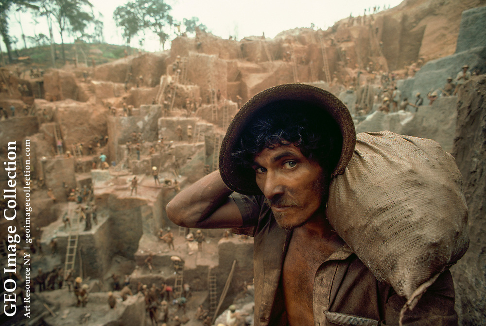 Miner carrying a sack of soil from a gold mine.