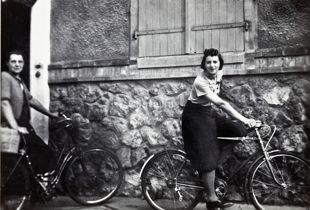 young adult woman on a men bicycle showing of her riding pants France 1950s