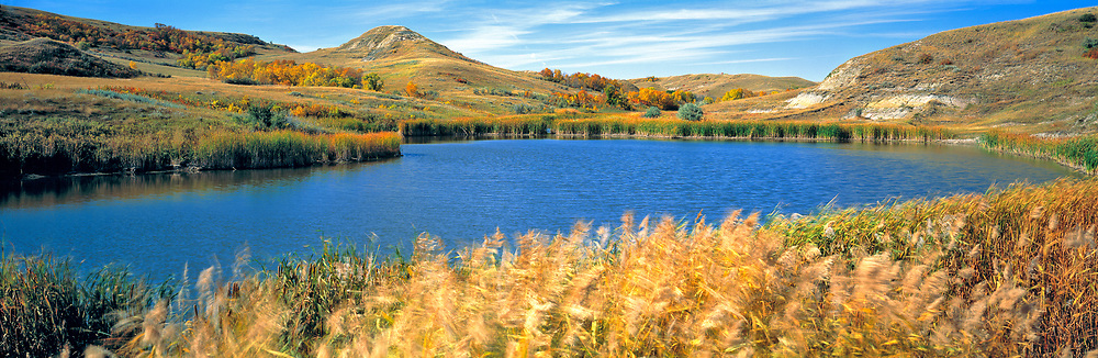 Autumn light slants over this deep blue pond in Lewis & Clark State Park, North Dakota