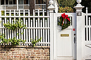 A garden garden gate decorated with a Christmas wreath on a historic home at Legare Street in Charleston, SC.