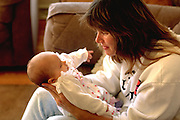 Mother age 35 playing with new born baby daughter.  Bloomington Minnesota USA