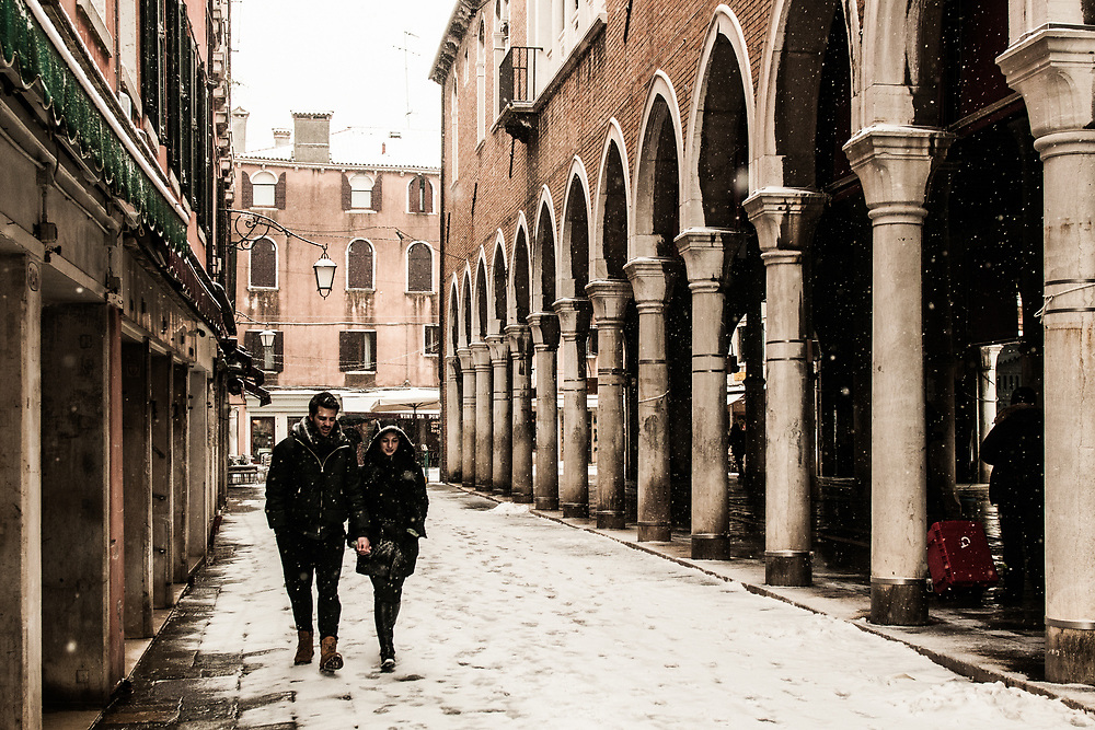"""VENICE, ITALY - 28th FEBRUARY/01st MARCH 2018<br /> A couple walk in the snow during a snowfall in Venice, Italy. A blast of freezing weather called the """"Beast from the East"""" has gripped most of Europe in the middle of winter of 2018, and in Venice A snowfall has covered the city with white, making it fascinating and poetic for citizen and tourists.   © Simone Padovani / Awakening"""