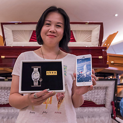Yean, founder of Skea which specializes in custom made paper gifts for the spirits - in her showroom near Taipei.<br /> <br /> Buddhists believe in the neverending cycle of life, death, and reincarnation. With consumerism taking its toll on our society, interdimensional love has also been redefined. Back in the days, it sufficed to send the deceased loved ones a stack of hell money or perhaps a slip of paper with imprinted clothing (including a scissors icon in case the size doesn't fit). But nowadays it seems incredibly important to upgrade to fancier donations for the ancestral spirits, and furthermore to ensure they can keep up with technological trends in their afterlife. Thus, people buy all sorts of lavish gifts made of paper mâché to honor the dead, not necessarily for the wandering spirits, as those are already appeased with the Pudu rites hold for them during Ghost Month. Besides the funerals, biweekly Bai-Bai tributes, and individual death anniversaries, the peak season for producers to sell their 3D paper imitations is the annual Tomb Sweeping Day Qingming. <br /> <br /> Skea is distributing meaningful and eco-friendly paper products via webshop all over Asia. The product range includes luxurious mansions with swimming pools, entertainment stuff such as entire discos, ice cream parlors, sports gear, plus every means of transport imaginable – sports cars, jets, bicycles, motorbikes. Skea also offers imitated electronic gadgets such as cameras, or phones and tablets where even the apps are designed by Skea. There's watches, jewelry, razors, perfumes, sunglasses, hats, the latest fashion (formal, traditional and casual dresses) – basically everything needed to dress swag and live comfy in the afterlife.<br /> <br /> Smaller presents like the latest sPhone 8plus (with 80 GB spiritual memory) is available for about USD 100, whereas an entire villa with all the trimmings goes for about USD 4.500