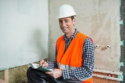 Germany, Munich, Portrait of construction worker taking notes
