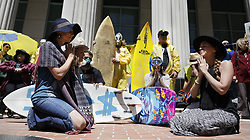 April 14, 2017 - San Diego, California, U.S. - People who want nuclear waste removed from the San Onofre Nuclear Generating Station gathered on the steps of San Diego Superior Court for a demonstration featuring a cappella singing, surfboards and speeches.  JESS MAGIC, left, and KRISTA RICHARDS of the group Heart Medicine, pray facing each other during a rally outside of the Hall of Justice during the rally. (Credit Image: © John Gastaldo via ZUMA Wire)
