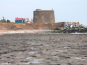 Rapid coastal erosion at East Lane, Bawdsey, Suffolk, England. Soft crag cliffs are easily eroded, dark underlying London clay is exposed. Rock armour imported from Scandinavia has been placed in front of the historic martello tower and some distance further along the coast to protect the buildings from erosion.