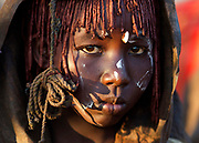 A Pokot girl covered in animal skins walks to a place where she will rest after having been circumcised, about 80 kilometres from the town of Marigat in Baringo County, Kenya, October 17, 2014. The ceremony starts the evening before the girls get circumcised and involves women and elders of the community gathering together, singing and dancing through out the night in encouragement to the girls who together wait inside a hut for first light. The traditional practice of circumcision within the Pokot is a right of passage that marks the transition to womanhood and a requirement to marriage within the community. Picture taken on October 17, 2014 REUTERS/Siegfried Modola (KENYA)