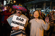 "New York, NY - 31 October 2016. A man wearing a serape and a sombrero carries a sign reading ""Bad Hombre"" next to someone in a Hillary Clinton costume in the annual Greenwich Village Halloween parade."