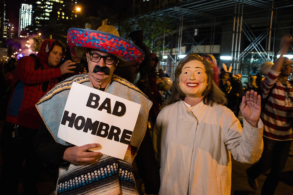 """New York, NY - 31 October 2016. A man wearing a serape and a sombrero carries a sign reading """"Bad Hombre"""" next to someone in a Hillary Clinton costume in the annual Greenwich Village Halloween parade."""