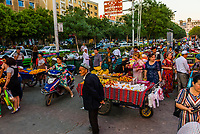 Street market outside the bazaar, Turpan, Xinjiang Province, China. Turpan is a small oasis town and former Silk Road outpost. Uyghur people are a Central Asian people of Muslim Turkic origin. They are China's largest minority group.