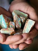 Handful of unrefined opals mined in Coober Pedy, South Australia, Australia