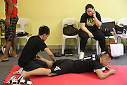 """Saiful Merican, 1st ranked WMA featherweight, massaged by trainer<br /><br />MMA. Mixed Martial Arts """"Tigers of Asia"""" cage fighting competition. Top professional male and female fighters from across Asia, Russia, Australia, Malaysia, Japan and the Philippines come together to fight. This tournament takes place in front of a ten thousand strong crowd of supporters in Pelaing Stadium. Kuala Lumpur, Malaysia. October 2015"""