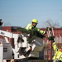City of Gallup Parks and Recreation workers Fred Frank (center), and D.R. Nelson (right) putting Christmas decorations up on light posts along Route 66, Monday Nov. 19 in Gallup.