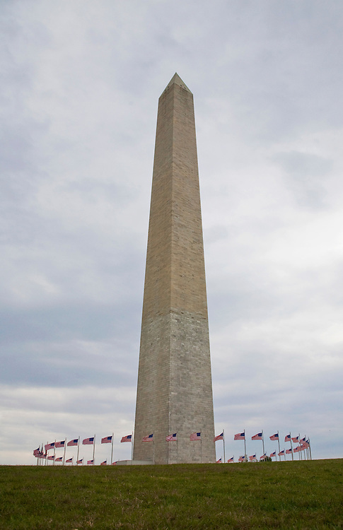 The Washington Monument with a circle of USA flags around its base.