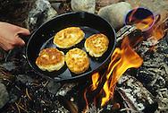 Cooking bannock over an open campfire