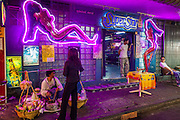 "Mar. 24, 2009 -- BANGKOK, THAILAND: A noodle vendor does business in front of the ""SuperStar Bar"" in the ""Patpong"" district of Bangkok. Patpong used to be Bangkok's red light district but it now presents a more ""family friendly"" atmosphere and the hard core red light districts have moved out to Soi Nana and Soi Cowboy on Sukhumvit Rd.    Photo by Jack Kurtz"