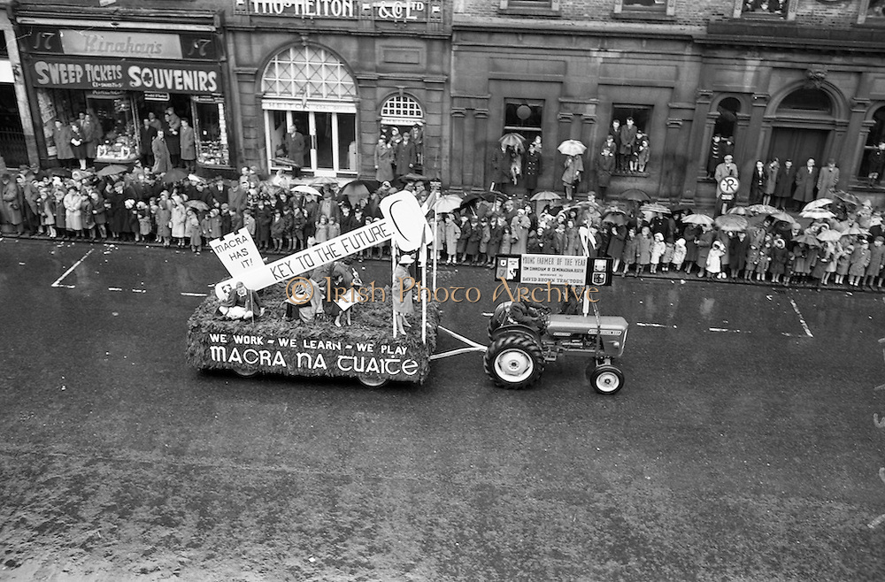 17/03/1963<br /> 03/17/1963<br /> 17 March 1963<br /> Tim Cunningham, Young Farmer of the Year from Co, Monaghan on a David Brown 880 tractor in the N.A.I.D.A. St. Patricks Day Parade, pulls a Macra float past the crowds, on Westmoreland Street, Dublin.