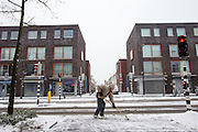 Een man ruimt de sneeuw voor een kruising bij de Amsterdamsestraatweg in Utrecht.<br />