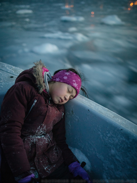 Laila sleeping. Sunday family fishing trip (arctic cod) in ice holes, with hunter Tobias Ignatiussen, his wife Silba, daughter Gerda and two friends Naima and Laila.<br /> Life in and around the Inuit settlement of Tasiilaq (population of 2000), in East Greenland.