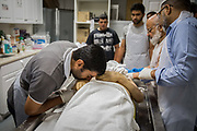 Amin Alsaloum, 27, kisses the hand of his deceased father, Riad Alsaloum, after washing the body in Islamic tradition with his brothers at a funeral home in Tampa, Florida, U.S. Riad Alsaloum's body was then placed in a casket and driven to a local mosque for prayer before burial.