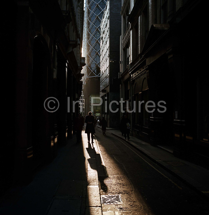 A businessman walks through late afternoon sunlight in a narrow lane in the City of London, the heart of the capital's financial district. A long shadow precedes the gentleman as he walks along this ancient street, now surrounded by modern corporate offices. The sunshine illuminates the pavement and road surfaces, the sun sinks between tall buildings in this, the capital's financial heart, founded by the Romans in 43AD.