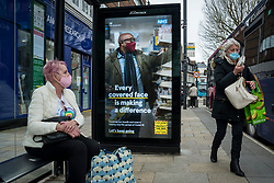© Licensed to London News Pictures. 25/02/2021. WATFORD, UK.  Women at a bus stop next to the UK Government's latest Covid-19 ad campaign which has been unveiled on digital screens in the town centre in Watford, Hertfordshire. The national ad campaign urges the public to continue with mask wearing, social distancing and hand washing.  England's stay at home order will remain in place until at least 29 March despite the minor easing of restrictions and the return of schools on 8 March.  Photo credit: Stephen Chung/LNP
